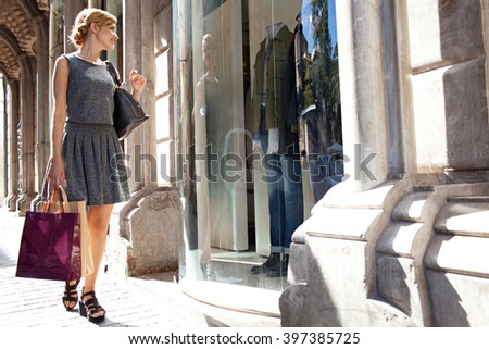 Beautiful young tourist woman carrying shopping bags walking in city with fashion stores, joyfully smiling and looking at shop windows, sunny outdoors. Consumer girl, exclusive lifestyle exterior.