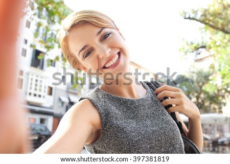 Beautiful young tourist woman joyful smiling, sightseeing holiday, holding smart phone to take selfies photos, fun expression outdoors. Portrait of girl using technology, consumer travel lifestyle. - stock photo