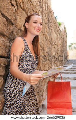 Beautiful young tourist woman visiting a destination city with old textured stone walls in a street, using a map, sightseeing on a summer holiday. Travel tourism and shopping on vacation, outdoors. - stock photo