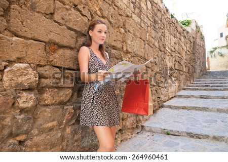 Beautiful young tourist woman visiting a destination city with rough old textured stone wall in a street with steps, using a map, sightseeing on holiday. Travel and shopping on vacation, outdoors. - stock photo