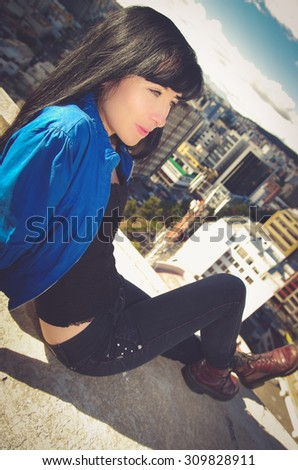 Beautiful young troubled  girl sitting on building roof looking at the city - stock photo