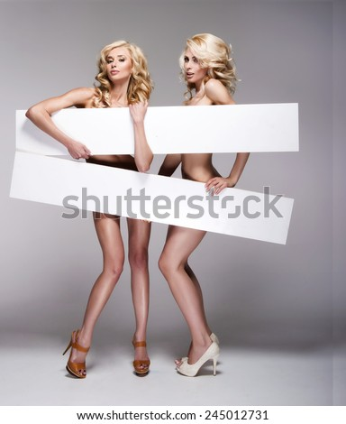 Beautiful young two women holding empty white board