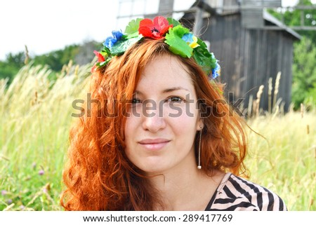 Beautiful young ukrainian redhead woman with flowers in her hair smiling happily with a mill at the background