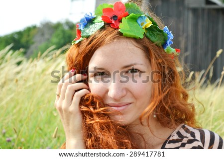 Beautiful young ukrainian redhead woman with flowers in her hair smiling happily with a mill at the background - stock photo