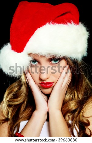 beautiful young upset woman dressed as Santa against black background - stock photo
