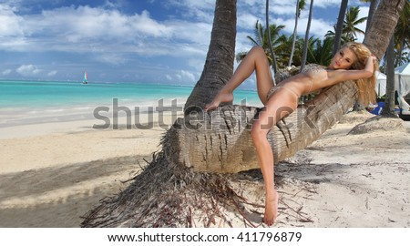 Beautiful young very sexy blond hair female model amazing girl lies on an old tree on the palm tree with an amazing view of the  sea  in the fleshy nude erotic crystal lingerie with long shapely legs - stock photo