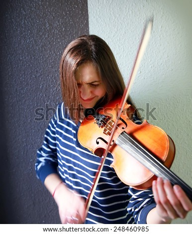 Beautiful, young violinist playing violin, close-up - stock photo