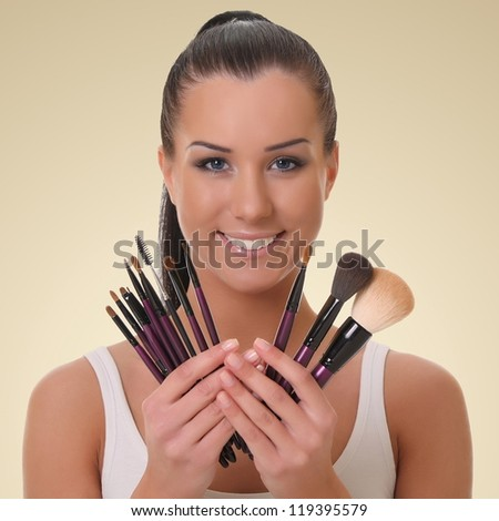beautiful young visagiste. on a brown background - stock photo