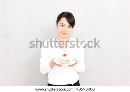 beautiful young waitress presenting plate of dessert - stock photo