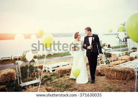 beautiful young wedding couple kissing , blonde bride with flower and her groom in summer park with sun haze - stock photo