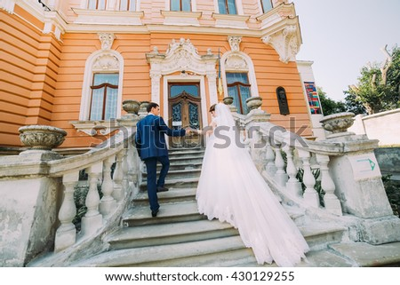Beautiful young wedding couple walking on stairs of romantic antique palace - stock photo