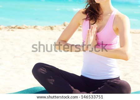 Beautiful young white female doing yoga at the beach - stock photo