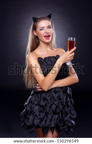 beautiful young winking woman with long hair in a fashion dress with cat ears on her head  and a glass of champagne in hand on a gradient background. Red lips.Fashion model. - stock photo