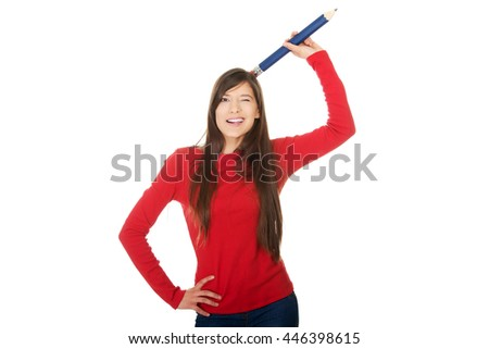 Beautiful young with a big pencil on head. - stock photo