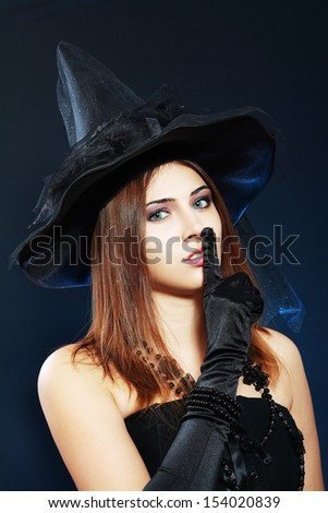 """beautiful young woma in witch or fairy costume and fancy hat for halloween party, showing """"hush!"""" sign holding finger on her lips over dark background - stock photo"""