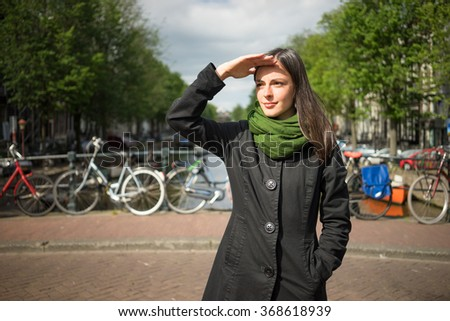Beautiful young woman admiring the beauty of Amsterdam on a bridge protect their eyes from sun with hand dressed in black coat and green scarf - stock photo