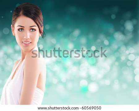Beautiful young woman against a bokeh background - stock photo