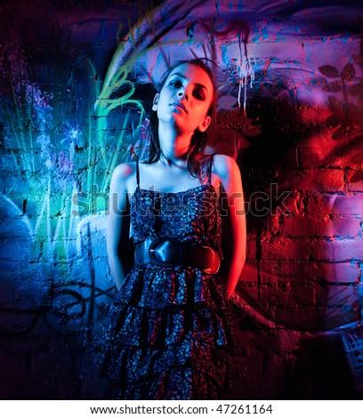 Beautiful young woman against graffiti wall. - stock photo