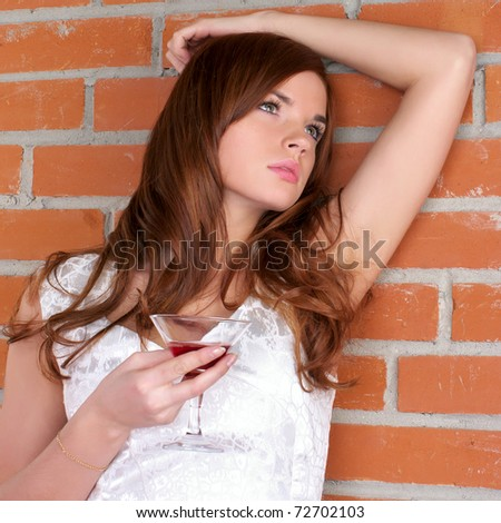 Beautiful young woman against red brick wall - stock photo