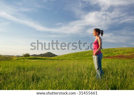 Beautiful young woman alone on a green field
