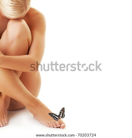 Beautiful young woman and butterfly sitting on her leg - stock photo