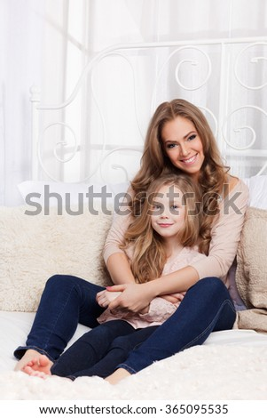 Beautiful young woman and child in the bed - stock photo