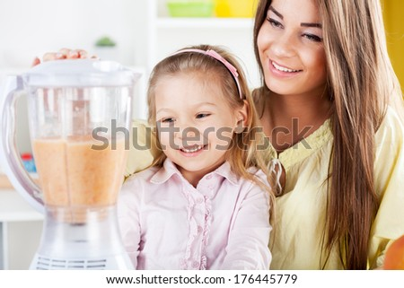 Beautiful young woman and cute little girl preparing healthy drink / meal in a blender in the kitchen. - stock photo