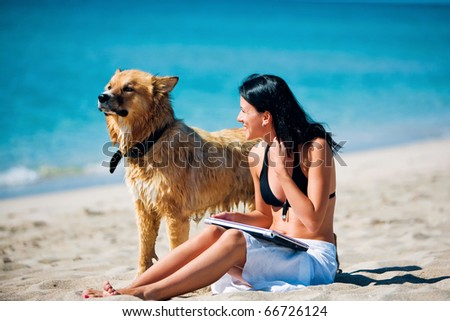 Beautiful young woman and dog on the beach - stock photo