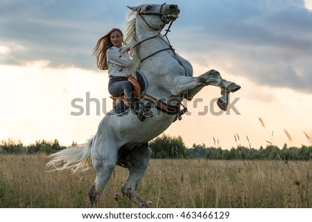 Beautiful young woman and gray horse in rack