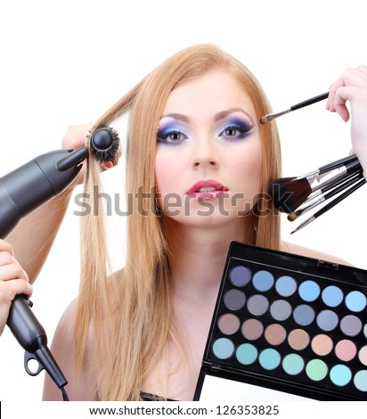 Beautiful young woman and hands with eyes shadows and hairdryer, isolated on white - stock photo