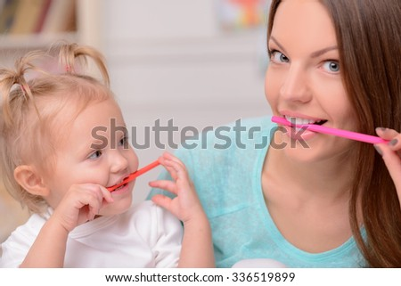 Beautiful young woman and her daughter are making fun. They are keeping colored pencils in their mouth. The mother and girl are smiling