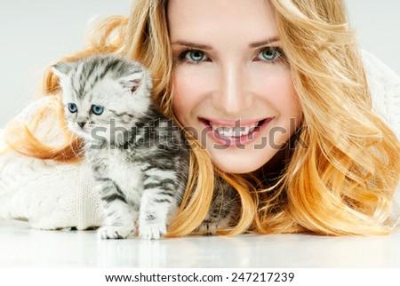 Beautiful young woman and her little kitten. Cute kitten. - stock photo