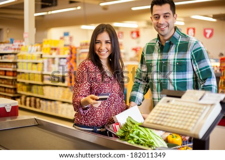 Beautiful young woman and her partner paying for groceries at the cash register with a credit card - stock photo