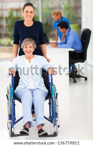 beautiful young woman and senior mother in doctor's office - stock photo