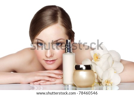 Beautiful young woman and skincare products - stock photo