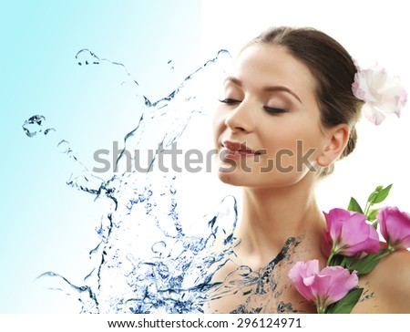 Beautiful young woman and water splash on light background - stock photo