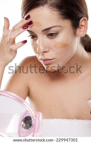 Beautiful young woman apply liquid base on her face - stock photo
