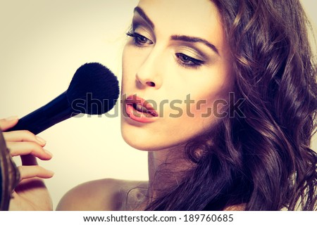 beautiful young woman apply makeup studio shot - stock photo