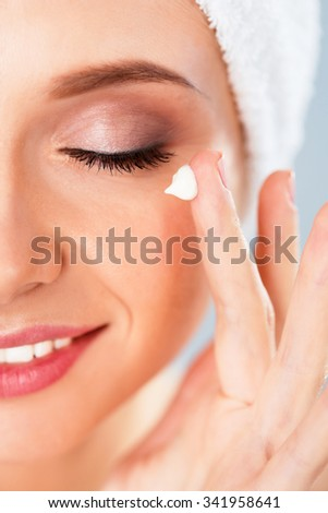Beautiful young woman applying a creme on her face isolated on gray background - stock photo