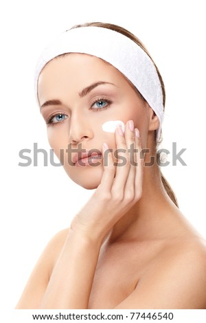 Beautiful young woman applying a creme on her face isolated on white background - stock photo