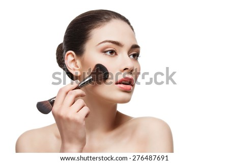 Beautiful young woman applying blush with two-sided brush. Isolated over white background. Copy space. - stock photo