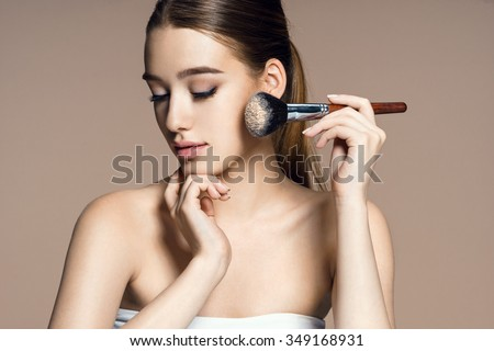 Beautiful young woman applying cosmetic powder on her face with tassel, skin care concept / photo composition of brunette girl on beige background - stock photo