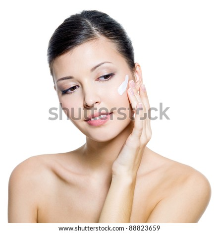 Beautiful young  woman applying  cream on face. Isolated on white background