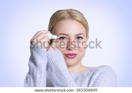 Beautiful young woman applying eye drops - stock photo