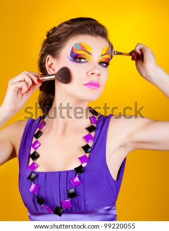Beautiful young woman applying eyeshadow on her face with make-up brush - stock photo
