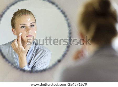 Beautiful young woman applying face cream - stock photo