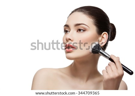 Beautiful young woman applying face powder with dual fiber brush. Isolated over white background. Copy space. - stock photo