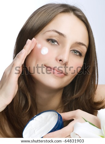 Beautiful Young Woman applying facial moisturizer.Skincare concept - stock photo