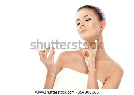 Beautiful young woman applying facial moisturizing cream.Head and shoulders shot.  - stock photo