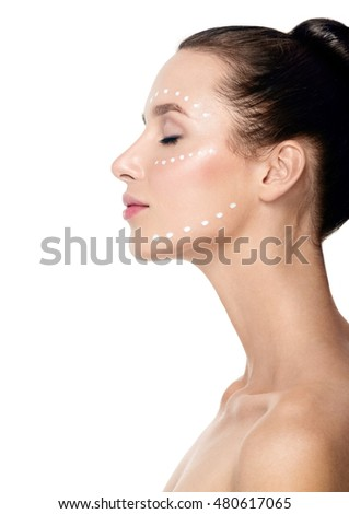 Beautiful Young Woman applying facial moisturizing cream.Skincare concept